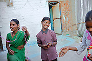 Poonam, 11, (centre) is smiling while helping her sister Jyoti, 12, (right) and their mother Sangita, 40, to decorate their newly built home before the celebrations for Diwali, the Hindu festival of lights, in Oriya Basti, one of the water-contaminated colonies in Bhopal, central India, near the abandoned Union Carbide (now DOW Chemical) industrial complex, site of the infamous '1984 Gas Disaster'.