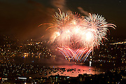 Spectacular fireworks explode over Gasworks Park, witnessed by a large audience of boats in Union Bay, at dusk July 4, 2007 in Seattle, Washington, USA.