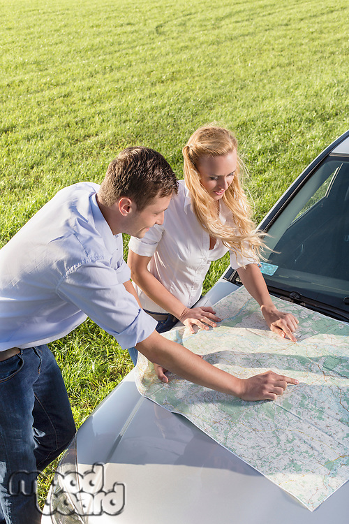 High angle view of couple reading map on car hood during road trip