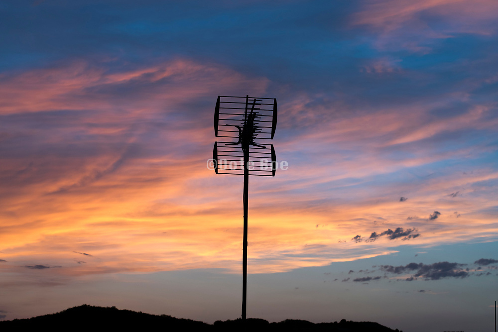 dramatic evening sky with an old style residential analog television antenna