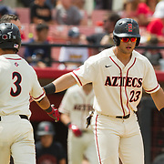 15 April 2018: San Diego State outfielder Chad Bible (23) congratulates teammate Jacob Maekawa (3) after he hit a sac fly to score Bible in the bottom of the third. The San Diego State baseball team closed out the weekend series against Cal State Fullerton with a 9-6 win at Tony Gwynn Stadium. <br /> More game action at sdsuaztecphotos.com
