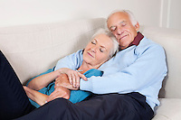 Romantic senior couple with arms around relaxing on sofa at home