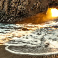 Sunset light through a sea arch on Pfeiffer Beach, Big Sur Coast, California.