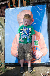 © Licensed to London News Pictures. 19/09/2011. Crays Hill, UK. A young stands next to a poster of himself at the entrance to Dale Farm, Essex  today (19/09/2011).  Activists and residents at the Dale Farm travellers site in Essex prepare for the council to enforce an eviction notice which is due to start today (19/09/2011). Photo credit: Ben Cawthra/LNP