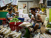 27 FEBRUARY 2019 - BANGKOK, THAILAND: Men package vegetables during the overnight shift in a Bangkok market. Bangkok, a city of about 14 million, is famous for its raucous nightlife. But Bangkok's real nightlife is seen in its markets and street stalls, many of which are open through the night.       PHOTO BY JACK KURTZ