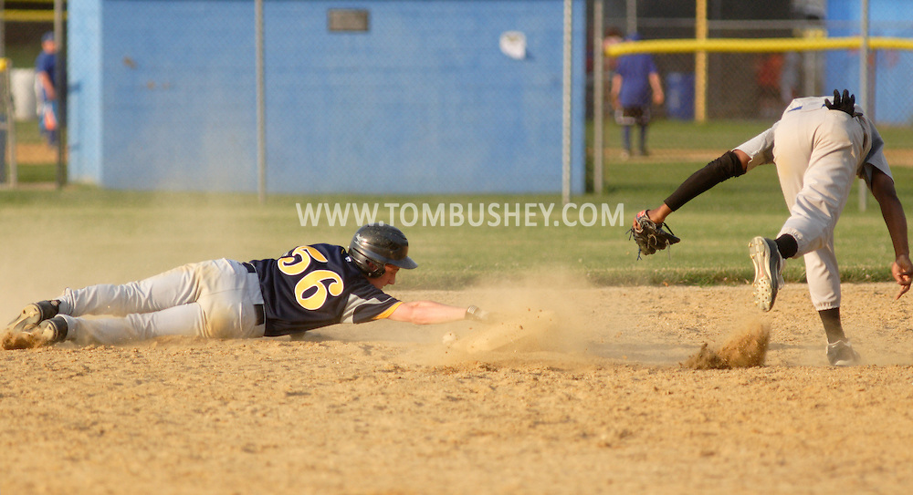 Middletown, NY - A baserunner reaches for second base as he slides past a fielder during a Collegiate League baseball game at Watts Park on July 2, 2008.