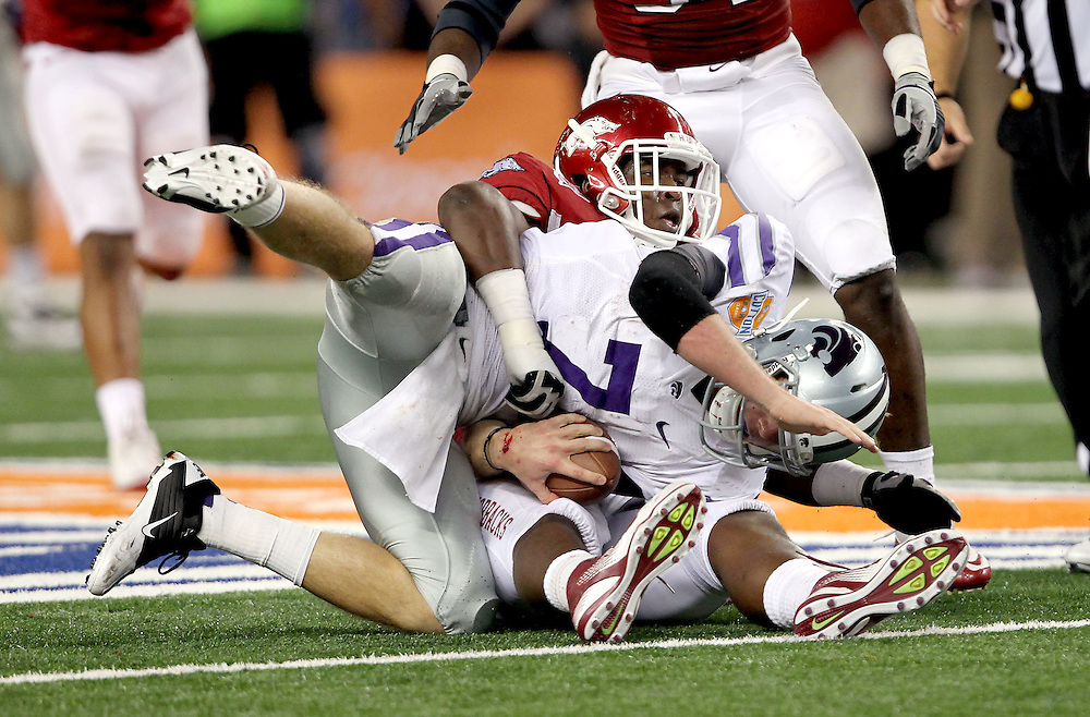 Arkansas defensive tackle Byran Jones (54) wraps up Kansas State quarterback Collin Klein (7) for a sack during the 2012 AT&T Cotton Bowl game between Arkansas and Kansas State at Cowboy Stadium in Arlington, Tx. on Jan 6th, 2012.