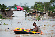 Dar es Salaam, Tanzania -   2015-05-07  - A man floats through the flooded Jangwani neighbourhood in Dar es Salaam, Tanzania on May 7, 2015.  The Tanzania Meteorological Agency warned of 50mm of rainfall on May 6 and 7 due to a low pressure system developing in the Indian Ocean.    Photo by Daniel Hayduk