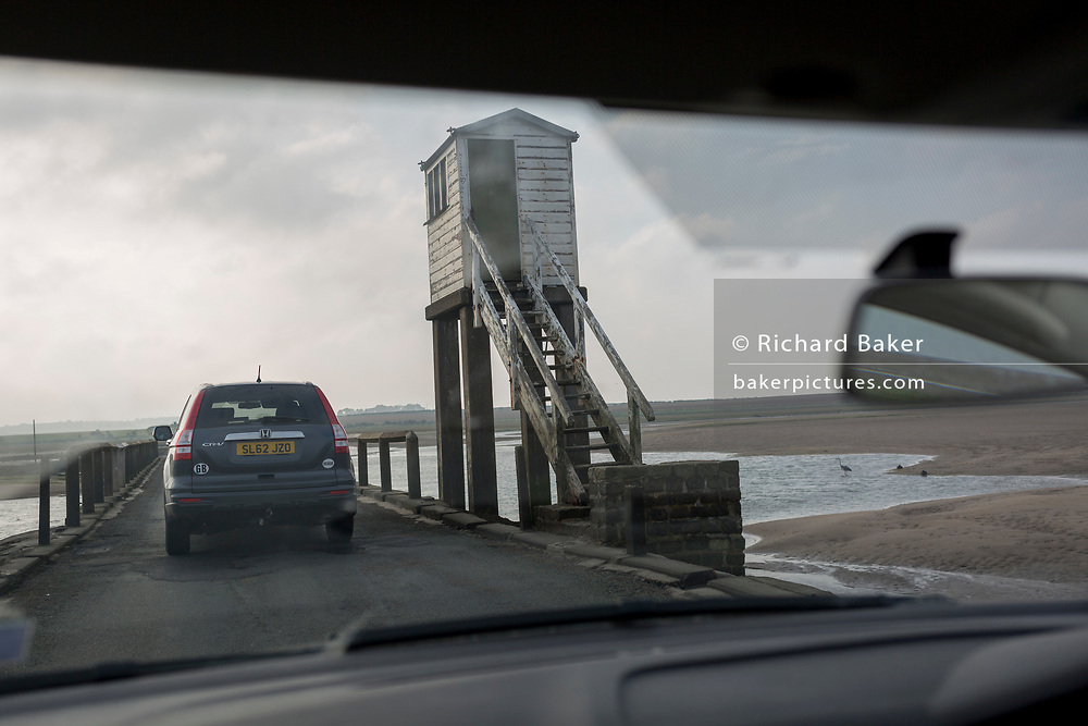 The view through a car's windscreen on the journey over the causeway between the tidal Lindisfarne island and the Northumbrian mainland, on 27th September 2017, on Lindisfarne Island, Northumberland, England. Despite tide timetables posted all over the area, drivers often mis-time their crossings, their vehicles ending up submerged in salt water. The small Lindisfarne population of just over 160 is swelled by the influx of over 650,000 visitors from all over the world every year. A tidal Island: Lindisfarne is a tidal island in that access is by a paved causeway which is covered by the North Sea twice in every 24 hour period. The Holy Island of Lindisfarne, also known simply as Holy Island, is an island off the northeast coast of England. Holy Island has a recorded history from the 6th century AD; it was an important centre of Celtic and Anglo-saxon Christianity. After the Viking invasions and the Norman conquest of England, a priory was reestablished.