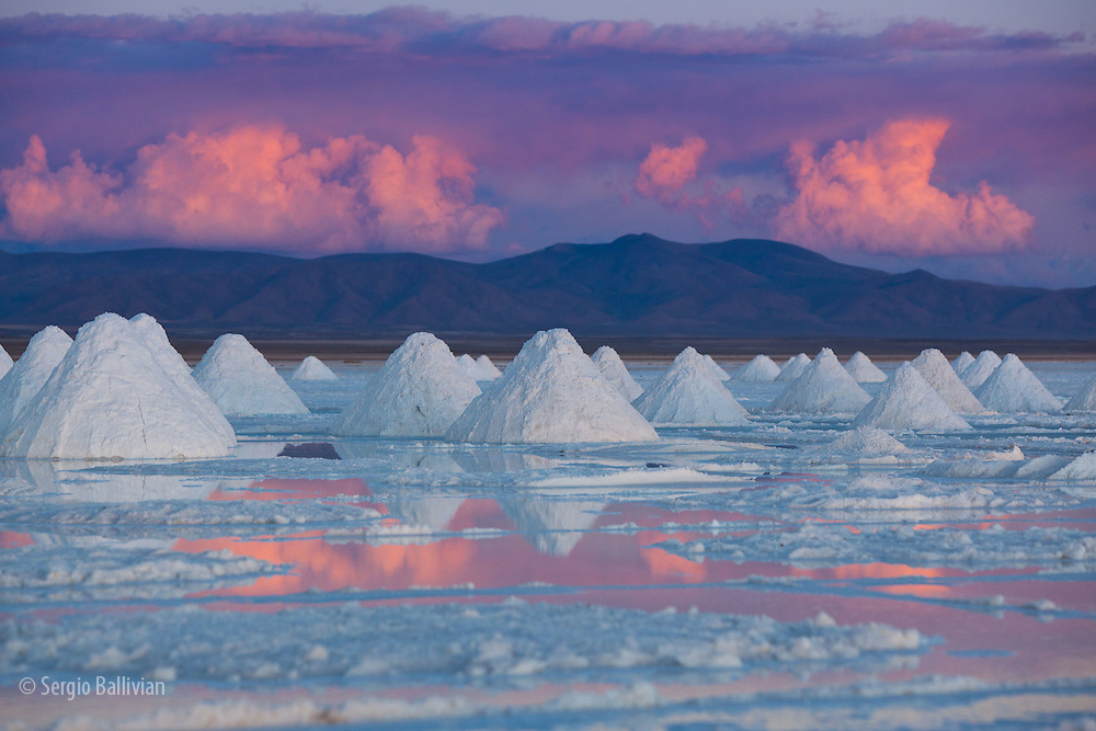 Pyramids of salt dry on the edge of the Salar de Uyuni on Bolivia's Altiplano at sunset.