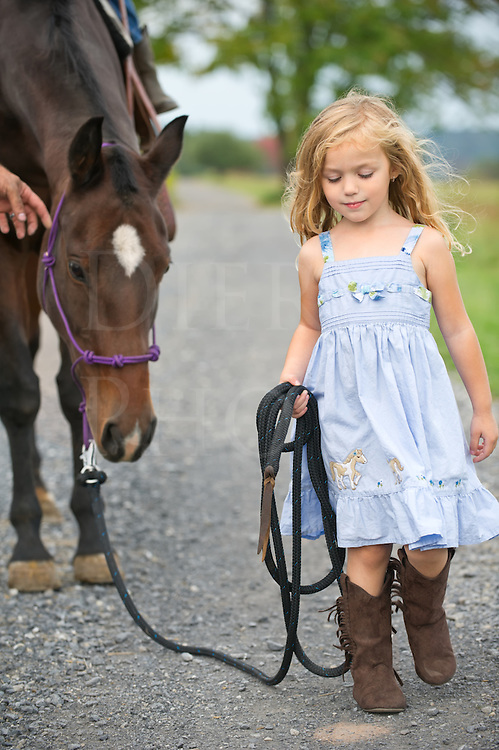 Little blonde girl leading her big horse down a country lane. Nikon D3s, 70-200mm.