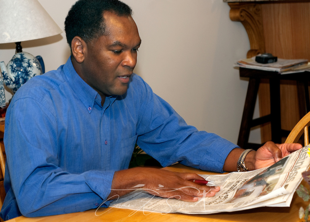 Levern Eady reads the business section of the Huntsville Times Oct. 27, 2009 at his home in Madison, Ala. Eady chose to relocate his family to the Huntsville metropolitan area for the intellectually-rich environment it provides for his children as well as the city's future economic potential. Analysts expect Huntsville to fare well in the new economy thanks to its strong aerospace, defense, and biotech industries. (Photo by Carmen K. Sisson/Cloudybright)