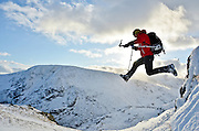 A fast shutter speed captures the action as a winter climber leaps from a snow covered ledge.