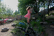 Girl swings on rope swing in risk averse playground called The Land on Plas Madoc Estate, Ruabon, Wrexham, Wales.