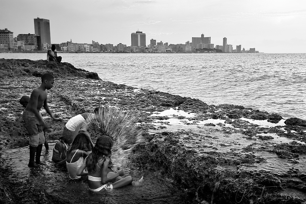 Children are playing at the waterfront of the Malecón in Havana.