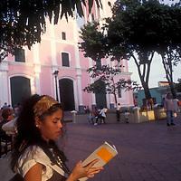 Mujer sentada leyendo libro en la plaza frente a Iglesia de Petare o Dulce Nombre de Jesús, Petare, Estado Miranda, Venezuela