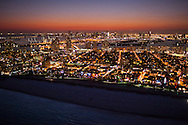 Art Deco Hotels with neon lights glowing along Ocean Drive on Miami Beach at twilight with the city of Miami Skyline in the distance.
