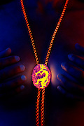 A glowing bolo draped across the bare chest of a woman who cups her breasts with her hands.Black light