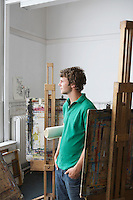Young male artist looking out of the window in art studio