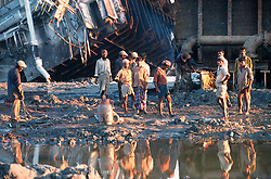 BANGLADESH CHITTAGONG MADHOM BIBIR HAT OCT00 - Labourers stand in the mud in front of giant cut-up pieces of metal, the only remainders of the once-decommissioned vessels.. .Several thousand labourers work on one medium-sized (50,000 ton) ship for a period of around three months, until it is completely dismantled and taken apart. ..Since Bangladesh does not possess mineral resources such as iron ore, it works out more cost-efficient to employ a large army of day-labourers to recycle the scrapped ships rather than to import ore. On average, a labourer can expect to earn a little more than 1 US Dollar per day...jre/Photo by Jiri Rezac..© Jiri Rezac 2000..Contact: +44 (0) 7050 110 417.Mobile: +44 (0) 7801 337 683.Office: +44 (0) 20 8968 9635..Email: jiri@jirirezac.com.Web: www.jirirezac.com..© All images Jiri Rezac 2000 - All rights reserved.