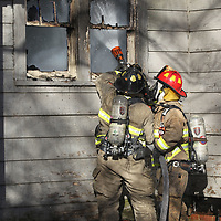Firemen use waterever access they can to try and knock down the flames at a house on Walker Street Monday morning.