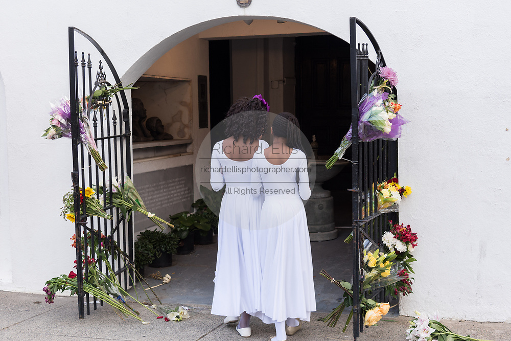Young members of the praise dance group of the Mother Emanuel African Methodist Episcopal Church view floral tributes left at the church on the 2nd anniversary of the mass shooting June 17, 2017 in Charleston, South Carolina. Nine members of the historic African-American church were gunned down by a white supremacist during bible study on June 17, 2015.