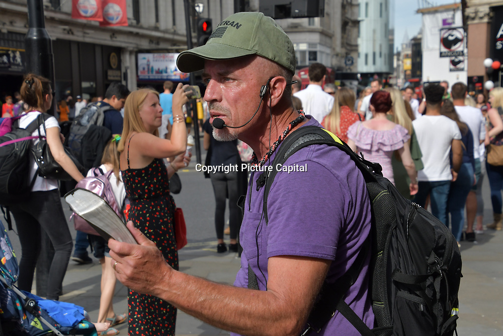 An aggressive Christian preacher with a loud microphone on people passing by we burn in hell only Jesus can saves you at Piccadilly Circus, on 1st June 2019, London, UK