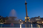 In late evening light, fountain spray drifts across Trafalgar Square  beneath Nelson's Column.