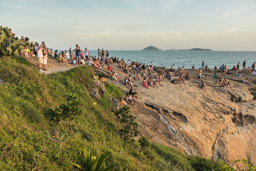 People gather to watch the sunset at Ipanema beac from Arpoar, RIo de Janeiro, Brazil.