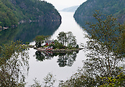 A red house and shed are built on a tiny island in Lovrafjord, southern Norway.
