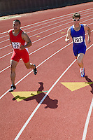 Male sprinters running on track