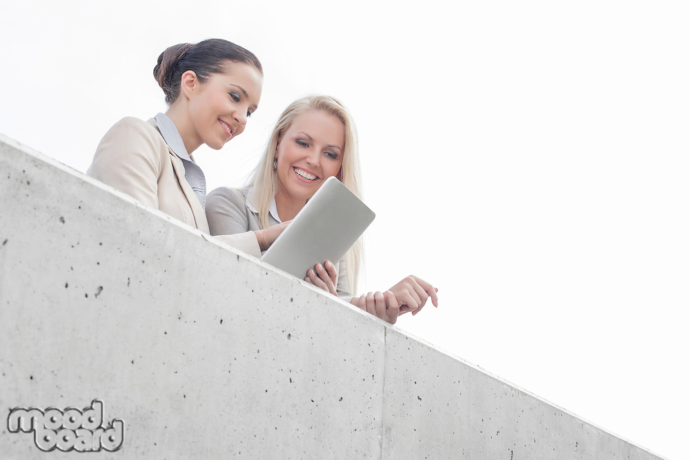 Low angle view of young businesswomen using digital tablet on office terrace against sky