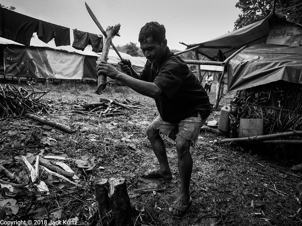 26 JANUARY 2018 - SANTO DOMINGO, ALBAY, PHILIPPINES: A man evacuated from his home on the slopes of the Mayon volcano chops firewood next to his temporary shelter in a field in Santo Domingo. The volcano was relatively quiet Friday, but the number of evacuees swelled to nearly 80,000 as people left the side of  the volcano in search of safety. There are nearly 12,000 evacuees in Santo Domingo, one of the communities most impacted by the volcano. The number of evacuees is impacting the availability of shelter space. Many people in Santo Domingo, on the north side of the volcano, are sleeping in huts made from bamboo and plastic sheeting. The Philippines is now preparing to house the volcano evacuees for up to three months.        PHOTO BY JACK KURTZ
