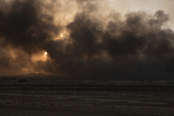 Licensed to London News Pictures. 02/11/2016. Qayyarah, Iraq. Plumes of smoke, rising from the Qayyarah Oilfield, blot out the afternoon sun.<br /> <br /> Two months after being liberated from the Islamic State, the Iraqi town of Qayyarah, located around 30km south of Mosul, is still dealing with the environmental repercussions of their ISIS occupation. The town's estimated 15,000 inhabitants constantly live under, and in, heavy clouds of smoke which often envelope the settlement. The clouds emanate from burning oil wells in a nearby oil field that were set alight by retreating ISIS extremists after a two year occupation. The proximity of the fires, often right next to homes within the town, covers many buildings and residents with thick soot and will lead to long term health and environmental implications. Photo credit: Matt Cetti-Roberts/LNP