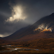 Winner of the 'Sunday Times Choice Award' - UK Landscape Photographer of the Year 2015. <br /> <br /> This was one of those special moments when the elements compose themselves before me like a fleeting gift<br /> to be grabbed in the brief moment its offered. I have lost count of the times opportunities have been<br /> forever lost while frantically getting into place and getting the camera set up. I noticed a break<br /> appearing in the heavy sky over Buachaille Etive Mor and a shaft of silvered light punctured through. It<br /> began to glide its way across Lairig Gartain and I started to shoot off frames hand held for fear of<br /> missing out by setting up the tripod. The ray of light began to glitter off the wet rock on the side of<br /> Stob nan Cabar and illuminated an lone angel-like cloud morphing over the Coupall,the reflection defined<br /> the river below perfectly.