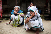 "(L-R: (blue) Saraswati Saha, 84; unnamed; and (white) Kamla Das, 90) Three elderly women who were the original refugees of The Partition recall being brought to Cooper's Camp on trains and trucks as they gather outside their homes in Cooper's Camp, Nadia district, Ranaghat, North 24 Parganas, West Bengal, India, on 19th January, 2012. ""The government will neither eat us nor spit us out."" says Kamla Das. ""They dropped us off here (in 1947) and I'm still here!"" Over 60 years after the bloody creation of Bangladesh in 1947, refugees who fled what was then known as West Pakistan to India still live as refugees, raising their children as refugees, and standing in line for government handouts..Photo by Suzanne Lee"