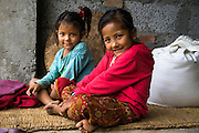 Monika (right) and her sister Aastha pose for a portrait in their temporary home in Chautara, Sindhupalchowk, Nepal on 29 June 2015. Monika (7), Aastha (6) and Sapana Baniya (2 months) lost their mother during the April 25th earthquake that completely levelled their house. Aastha was buried under the rubble together with her mother but Aastha survived. As their father Ratna Baniya (28) cannot care for the children on his own, SOS Childrens Villages has since been supporting their grandmother Bhagawati Baniya (56) with financial and social support so that she can manage to raise the children comfortably and ensure that they will all be schooled. Photo by Suzanne Lee for SOS Children's Villages
