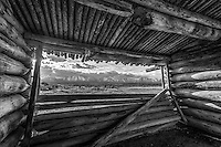 The window view in black and white of the Teton Mountain Range in Grand Teton National Park as seen from the center room of Cunningham Cabin, an old log cabin from the early settlers to the park.