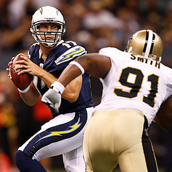 August 27, 2010; New Orleans, LA, USA; San Diego Chargers quarterback Philip Rivers (17) is rushed by New Orleans Saints defensive end Will Smith (91) during the first half of a preseason game at the Louisiana Superdome. The New Orleans Saints defeated the San Diego Chargers 36-21. Mandatory Credit: Derick E. Hingle
