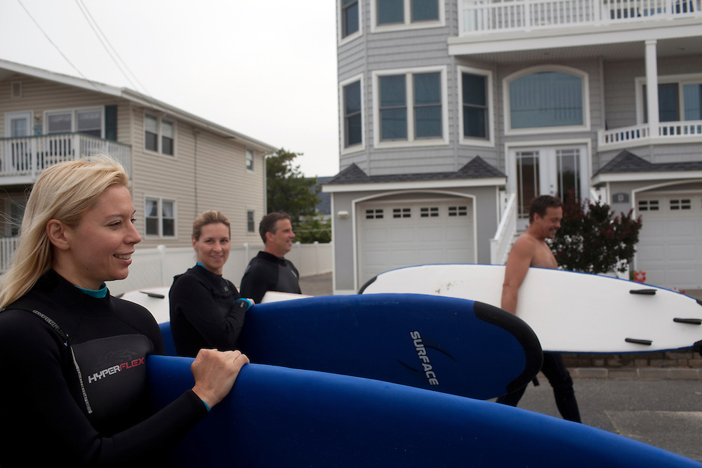 Long Beach Island, NJ - June 30, 2013 :  From left; Cathy Carey, from Beach Haven, Lila Walerych, from New York, surfing instructor Eric Leonard and Brighton Beach Surf Shop owner Mike Lisiewski make their way to the Brighton Beach for a surf lesson on Long Beach Island, NJ on June 30, 2013. People are returning to the beaches for the summer after recovery efforts post Superstorm Sandy.