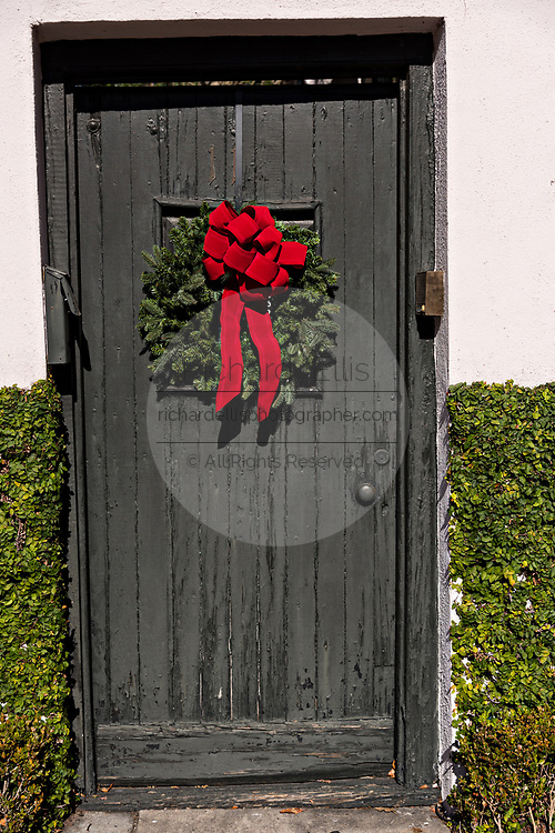 A black wooden door on a historic home decorated with a Christmas wreath on King Street in Charleston, SC.