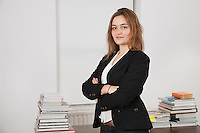Portrait of smiling young businesswoman with stack of books on desk in office