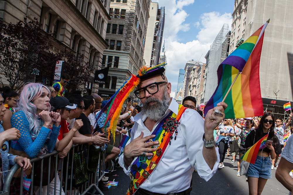 New York, NY - 30 June 2019. The New York City Heritage of Pride March filled Fifth Avenue for hours with participants from the LGBTQ community and it's supporters. A man bedecked in rainbows poses for the camera.