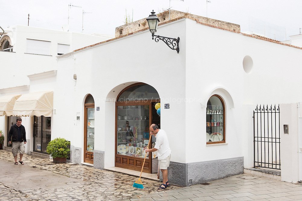 ANACAPRI, ITALY - 22 JULY 2014: A store owner sweeps the street after a storm  in Anacapri, a small comune on the island of Capri, Italy, on July 22nd 2014.<br /> <br /> New York City Mayor Bill de Blasio arrived in Italy with his family Sunday morning for an 8-day summer vacation that includes meetings with government officials and sightseeing in his ancestral homeland.