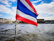 28 OCTOBER 2014 - BANGKOK, THAILAND: A Thai flag flies on a ferry crossing the Chao Phraya River between the Bangkok side of the river and the Thonburi side of the river.   PHOTO BY JACK KURTZ