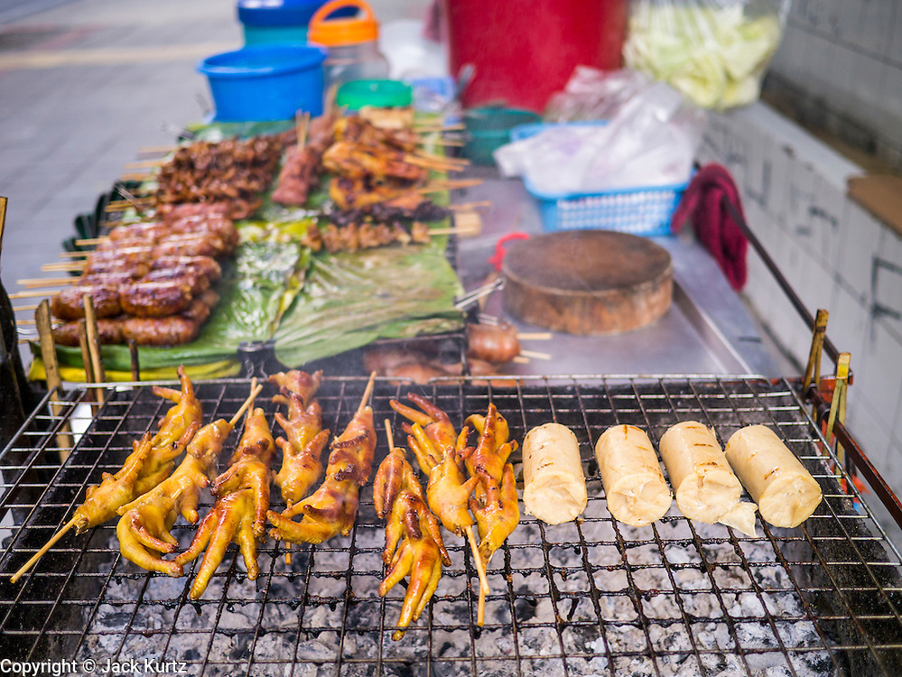 "04 OCTOBER 2012 - BANGKOK, THAILAND: A grilled meat vendor's stand on Sukhumvit Rd in Bangkok, Thailand. Thailand in general, and Bangkok in particular, has a vibrant tradition of street food and ""eating on the run."" In recent years, Bangkok's street food has become something of an international landmark and is being written about in glossy travel magazines and in the pages of the New York Times.       PHOTO BY JACK KURTZ"