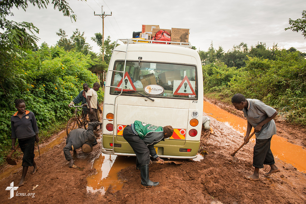 Volunteers attempt to free a bus carrying the Medical Mercy Team from deep mud on a road Tuesday, June 10, 2014, in rural Kakmega County, Kenya. The team walked to the clinic and the bus was freed several hours later. LCMS Communications/Erik M. Lunsford