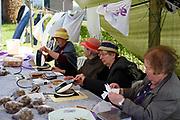 Vrouwen vermaken zich met de verkoop van wafels op een brochante in het plaatsje Warnsveld, Gelderland.