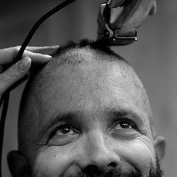"""The Rev. Quigg Lawrence (right) from the Church of the Holy Spirit in Roanoke County prepares looks in a mirror as he has his head shaved by Sharon Mirtaheri (left from Angels with Scissors) at the Roanoke Rescue Mission on Thursday. Quigg pledged to be shaved as """"bald as a cue ball"""" if $50,000 in donations were raised for the Rescue Center in three weeks."""