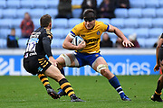 Bath back row Josh Bayliss (7) carries the ball under pressure from Wasps flyhalf Jimmy Gopperth (12) during the Gallagher Premiership Rugby match between Wasps and Bath Rugby at the Ricoh Arena, Coventry, England on 2 November 2019.